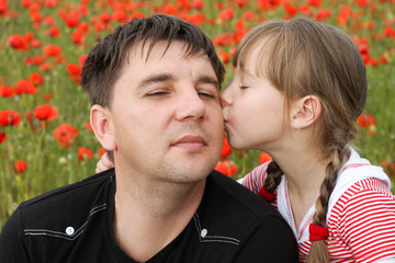 Girl kissing on the cheek father