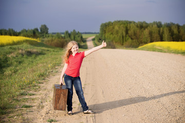 Smiling little girl holding a suitcase on a country road