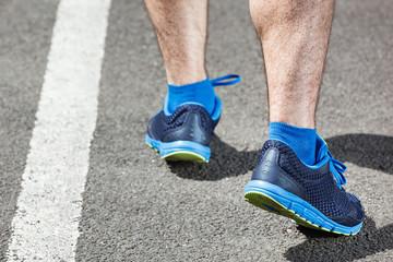 Runner feet running on stadium closeup on shoe.