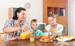 couple with son having breakfast with croissants in morning