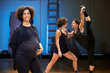 Pregnant woman teaching dance to students in theatre