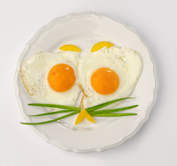 white plate with two fried eggs isolated on white background