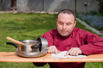 Chef looking in a recipe book, isolated
