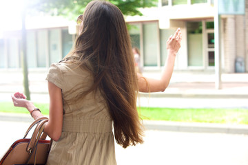 Stylish young woman waving for a taxi