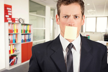 Young businessman with blank note on his mouth, inside office