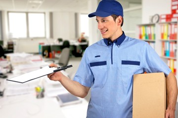Smiling delivery man, holding clip board and carton box