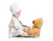 baby girl playing doctor with plush toy