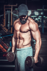 Muscular bodybuilder doing exercises with dumbbells