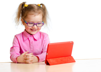 smiling kid in glasses looking at mini tablet pc screen sitting