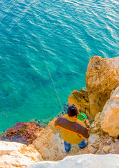 amateur fisherman fishing over the stones in Greece