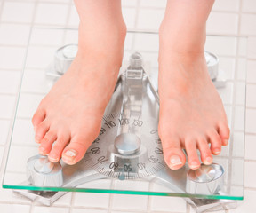 pair of female feet standing on a bathroom scale