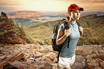 Young woman climber with backpack hiking in mountain