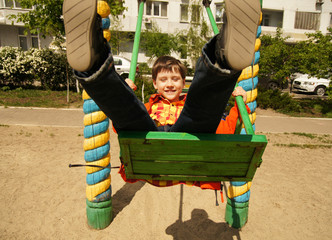 Boy riding on a swing