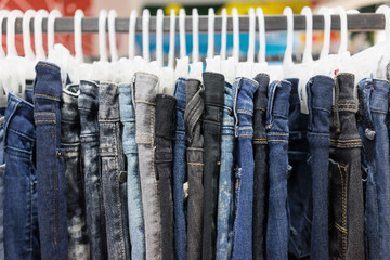 Jeans is hanged on rack.
