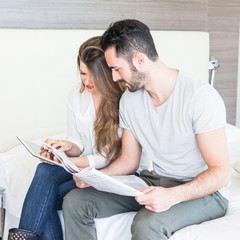 Couple with Digital Tablet and Newspaper