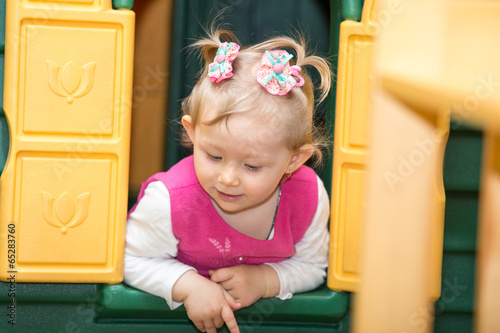 Little child girl playing in kindergarten in Montessori
