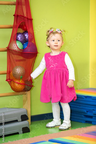 Little child girl playing with ball in kindergarten