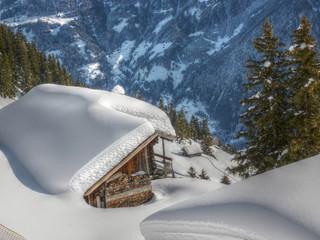 Schihütte mit Feuerholz in den Alpen in HDR