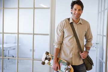Casual businessman standing with his skateboard smiling at camer