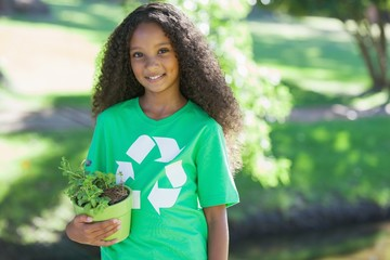 Young environmental activist smiling at the camera holding a pot