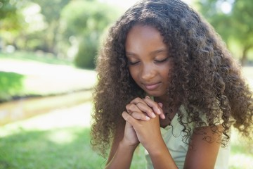 Young girl praying in the park