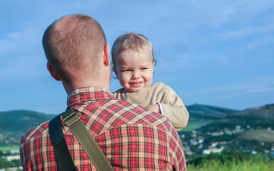 Toddler boy on the shoulder of his father