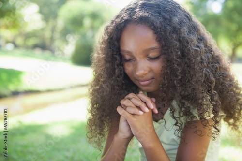 Young girl praying in the park - 65286781