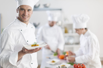 chef presenting a dish with his team in background