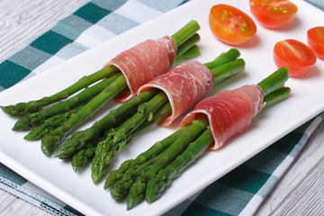Green asparagus wrapped in ham on a white plate top view