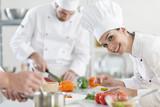 female chef preparing a dish in a professional kitchen