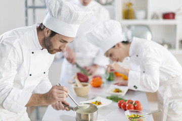 chef preparing a dish his team in the background