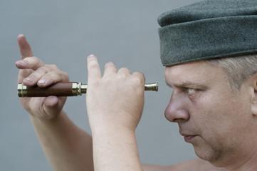 man holding  a spyglass