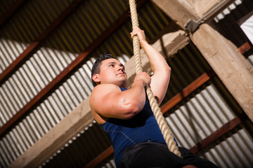 Climbing a rope at a gym