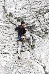 Man climbing natural rocky wall.
