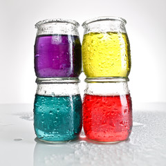 photography closeup glass jars of colored water stacked
