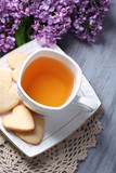 Lavender cookies and cup of tasty tea on color wooden