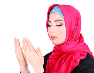 Beautiful muslim arabic woman praying on grey background