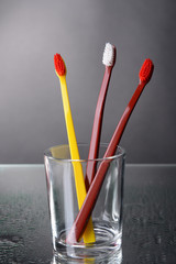 Toothbrushes in glass on grey background