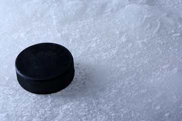 Black hockey puck on ice rink background