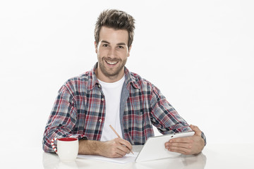 handsome young man using a digital tablet and paper