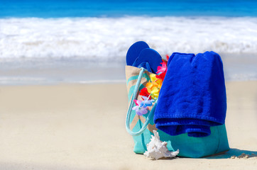 Beach bag with flip flops by the ocean