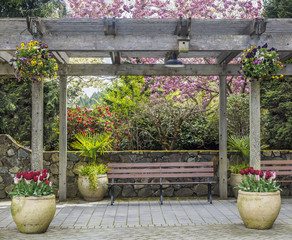 Rustic pergola with bench and flower pots