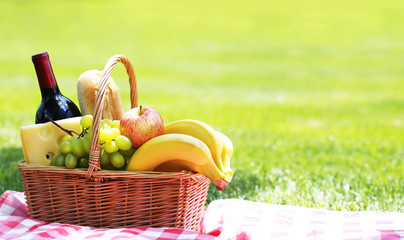 Picnic basket with food on green grass