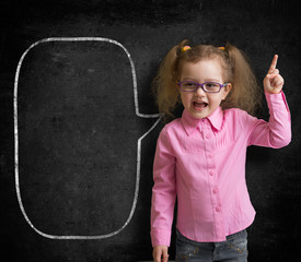 Funny child in eyeglasses standing near school chalkboard  as a