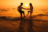 Fototapety couple having fun in the sea at sunset beach