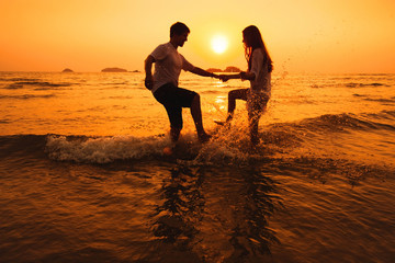 couple having fun in the sea at sunset beach