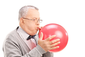 Mature man blowing up a balloon