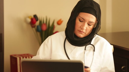 Female doctor writing  prescription with computer