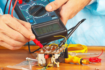 Serviceman checks electronic components with multimeter