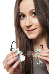 young woman cleans her glasses with a tissue